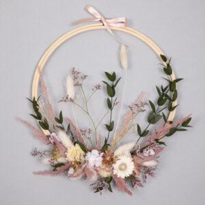Composition de fleurs séchées tendue sur tambour de broderie dans les tons roses